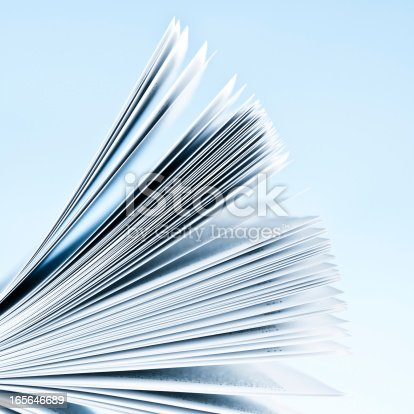 Close-up of magazine pages on light blue background. Shallow depth of focus.