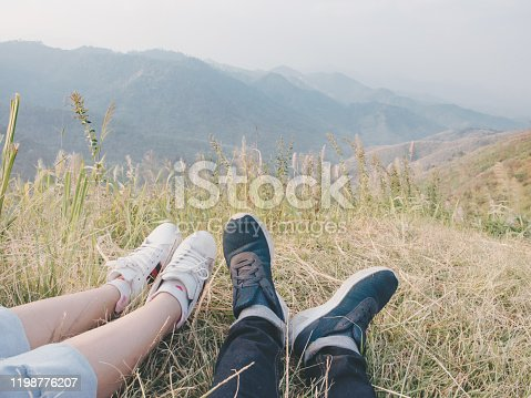 Close-up of male and female's feet relaxing in nature and landscapes beautiful mountains.