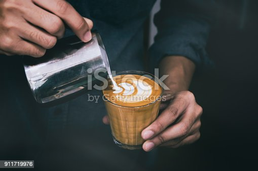 istock Close-up of male barista hand holding and pouring hot milk for prepare latte art on piccolo latte cup of coffee. 911719976