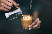 Close-up of male barista hand holding and pouring hot milk for prepare latte art on piccolo latte cup of coffee. vintage color tone.