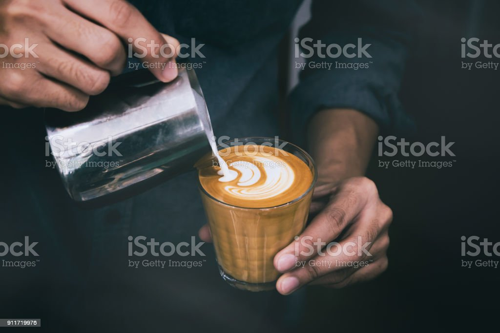 Close-up of male barista hand holding and pouring hot milk for prepare latte art on piccolo latte cup of coffee. stock photo