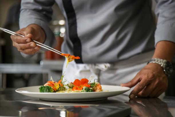 closeup of male chef arranging edible flowers on the meal in the commercial kitchen - przybranie zdjęcia i obrazy z banku zdjęć