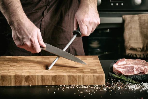 erkek şef el closeup büyük bir şef bıçağı keskinleştirmek - murfak bıçağı stok fotoğraflar ve resimler