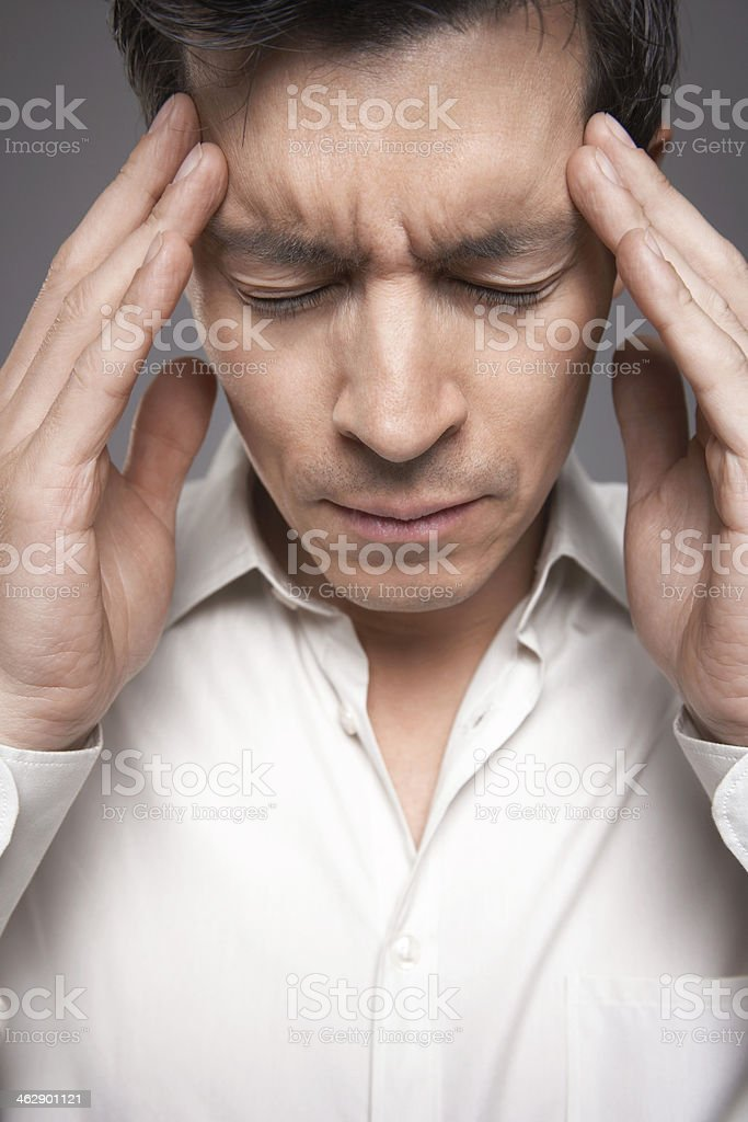 Closeup Of Male Executive With Fingers Pressed To Forehead royalty-free stock photo