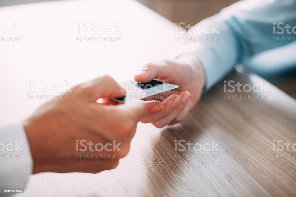 Close-up of male hand giving credit card - Photo