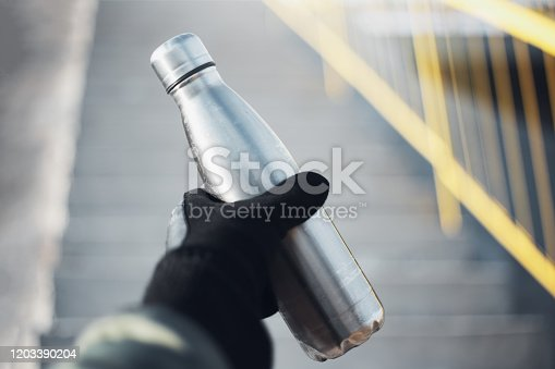 1129148925 istock photo Close-up of male hand holding dressed black glove, holding used reusable steel thermo water bottle on blurred background of urban stairs. 1203390204