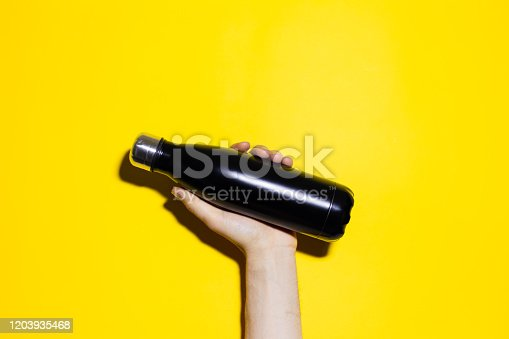 1129148925 istock photo Close-up of male hand holding reusable steel thermo water bottle of black color. Isolated on yellow background. 1203935468