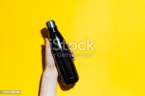 1129148925 istock photo Close-up of male hand holding reusable steel thermo water bottle of black color. Isolated on yellow background with copy space. 1204188356