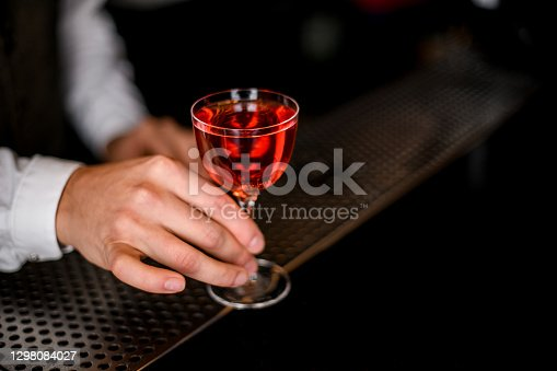 close-up of male hand carefully holding transparent glass with bright red alcoholic drink at blurred background