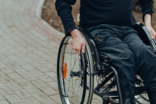 Close-up of male hand on wheel of wheelchair during walk in park. He holds his hands on the wheel. Close-up of male hand on wheel of wheelchair during walk in park. He holds his hands on the wheel. paraplegic stock pictures, royalty-free photos & images