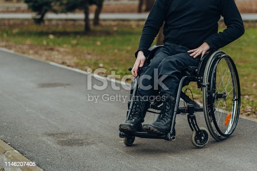 Close-up of male hand on wheel of wheelchair during walk in park. He holds his hands on the wheel.