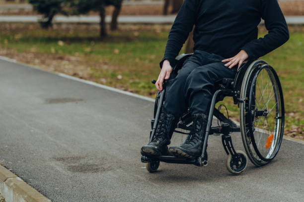 Close-up of male hand on wheel of wheelchair during walk in park. He holds his hands on the wheel. Close-up of male hand on wheel of wheelchair during walk in park. He holds his hands on the wheel. paralysis stock pictures, royalty-free photos & images