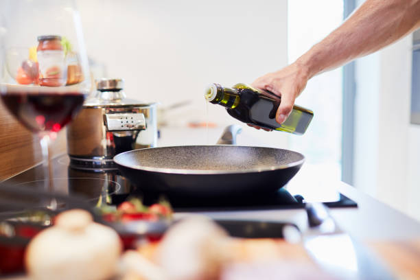 Close-up of male hand pouring oil into pan in the kitchen stock photo
