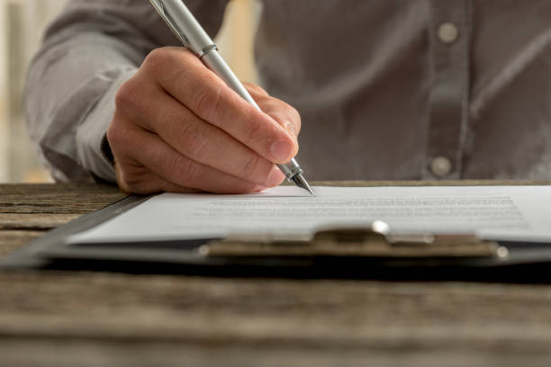 closeup of male hand signing business contract or document - testimonial stock photos and pictures
