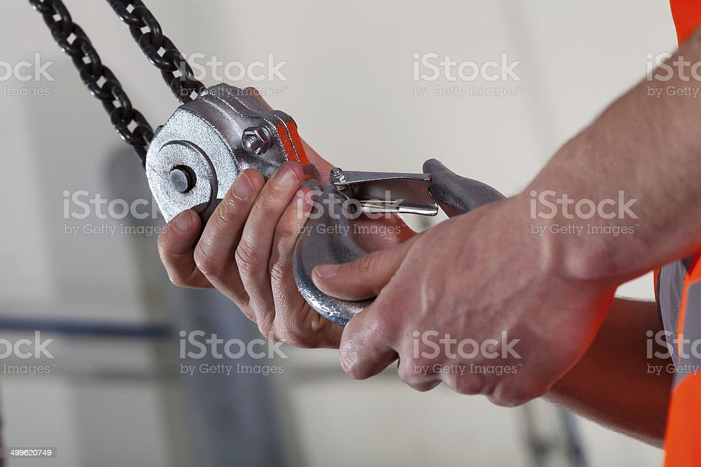 Close-up of male hands and lifting hook stock photo