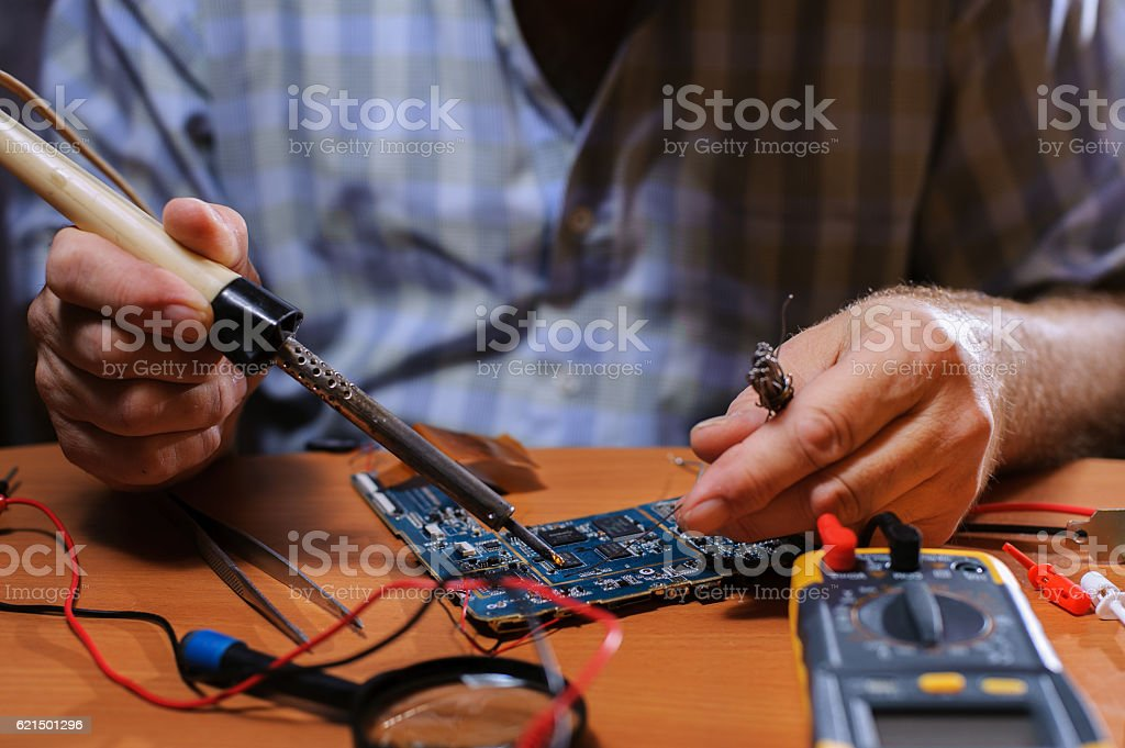 Closeup of male hands soldering computer board. stock photo