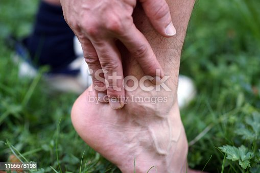 867056016istockphoto Close-up of male hands touching ankle after injury while exercising and running 1155578196