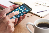 istock Closeup of male hands touching smartphone screen for using app at table. 1142528983