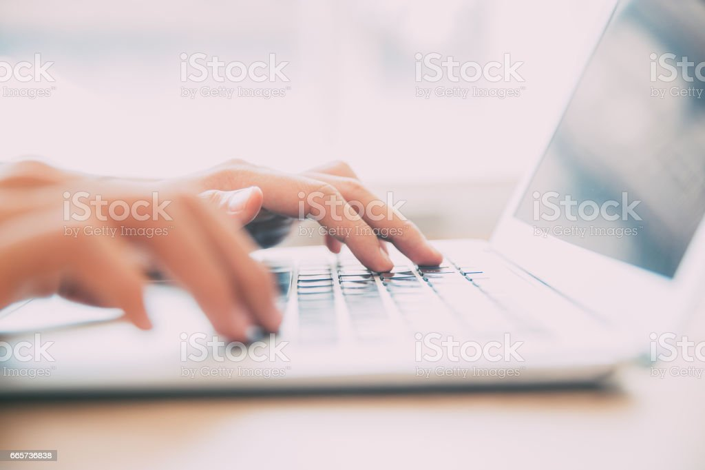 Close-up of male hands typing on laptop keyboard stock photo