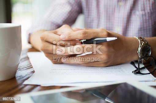 istock Close-up of male hands with pen on table 692732572