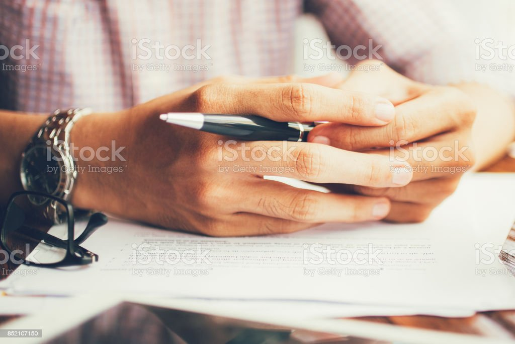 Close-up of male hands with pen on table stock photo