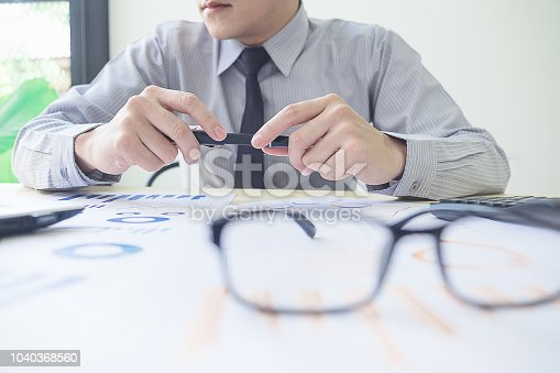 istock Close-up of male hands with pen over document Businessman analyzing investment charts. Accounting 1040368560