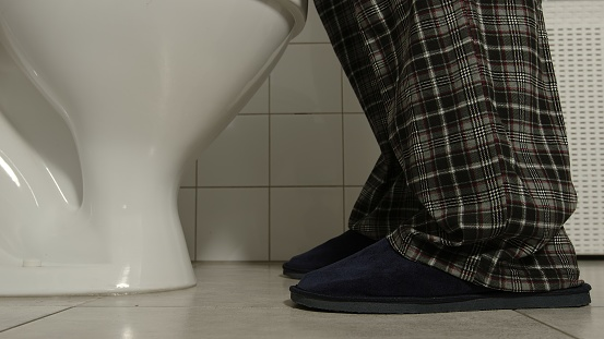 Closeup of male legs in a pajamas and slippers comes to a toilet