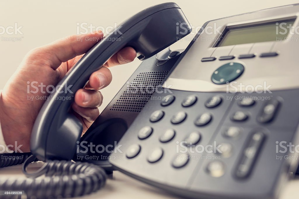 Closeup of male operator about to answer a phone call stock photo