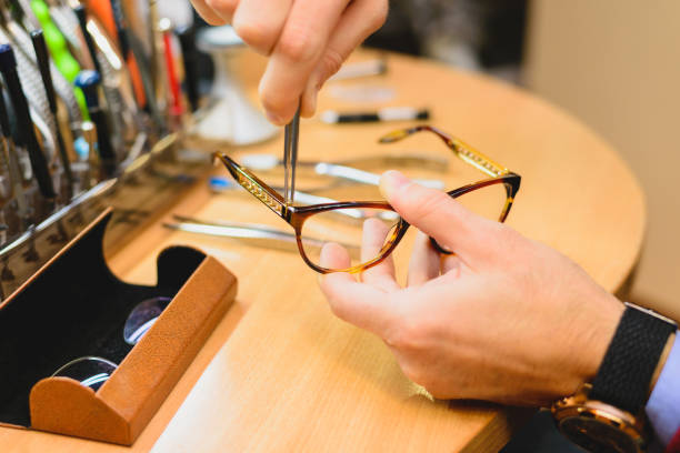 Closeup of male optician's hands repairing eyeglasses Closeup of adult caucasian male optician hands repairing eyeglasses using specialized tools lens optical instrument stock pictures, royalty-free photos & images
