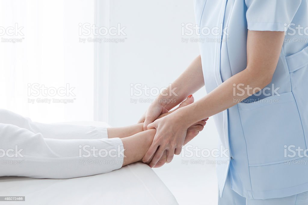 Close-up of male physiotherapist massaging the leg of female patient stock photo
