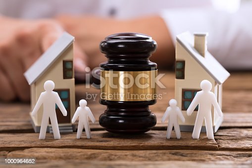 istock Close-up of mallet showing separation of family and house 1000964652