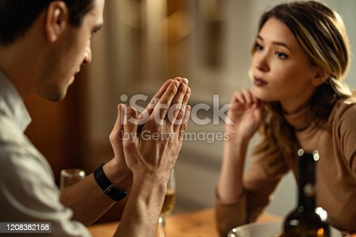 Close-up of man with hands clasped begging his girlfriend for forgiveness.