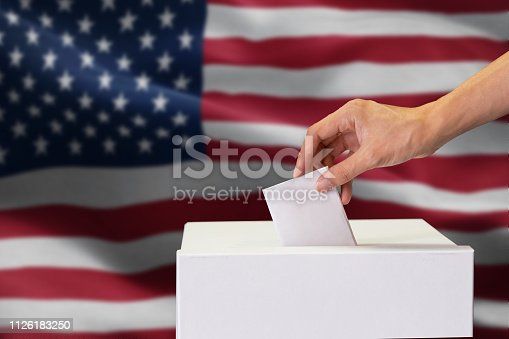 1157022917 istock photo Close-up of man casting and inserting a vote and choosing and making a decision what he wants in polling box with United States flag blended in background. 1126183250