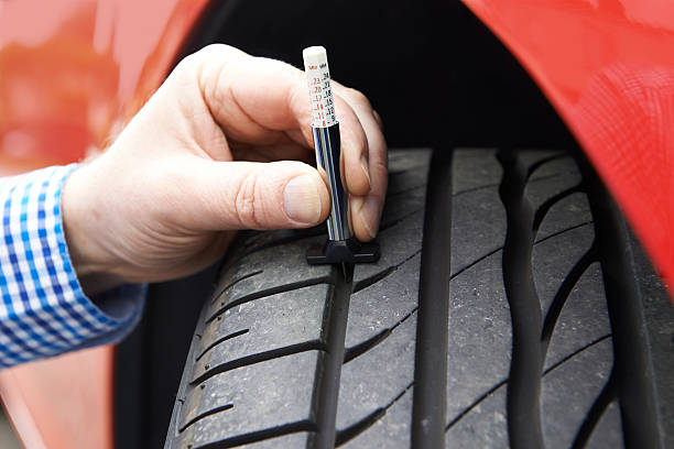Primer plano de hombre de comprobación en automóvil de rodadura de los neumáticos con manómetro - foto de stock