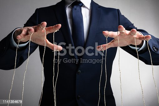 istock Close-up Of Man Controls The Puppet With Fingers 1141354679