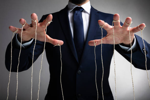Close-up Of Man Controls The Puppet With Fingers Man's Hand Controls The Puppet With The Fingers Attached To Threads Against Gray Background puppet stock pictures, royalty-free photos & images