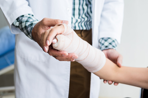 Close-up of man doctor of checking splint the arm of female patient hand due to with her arm broken for better healing with a smile sit in a wheelchair In the room hospital background.