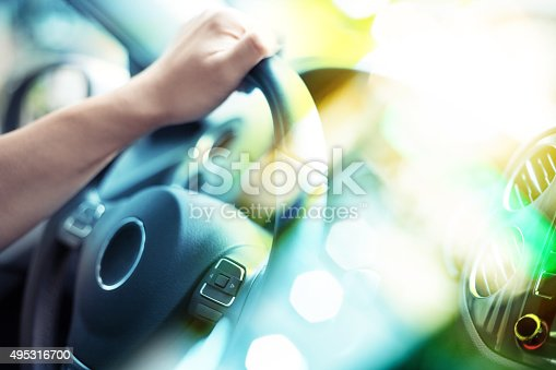 Closeup of Man Driving a Car Hand on Steering Wheel, defocused lights shining through window shield.