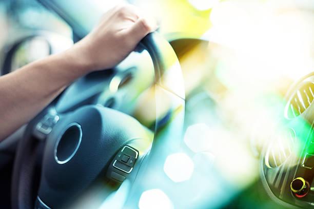 Closeup of Man Driving a Car Hand on Steering Wheel stock photo