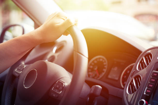 Close-up of Man Driving a Car Hand on Steering Wheel stock photo