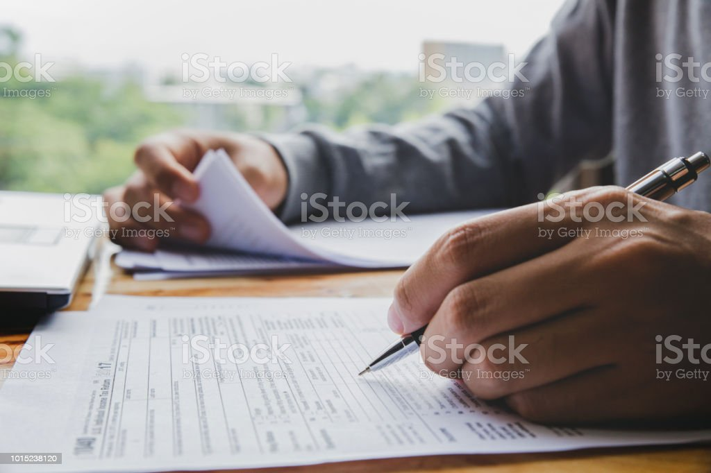 Closeup of man hand filling income tax forms stock photo