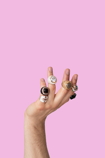 Close-up of man hand with female jewelry over pink background. Isolated man hand wearing woman rings on fingers, with copy space. Cross dressing unrecognizable person concept with negative space.