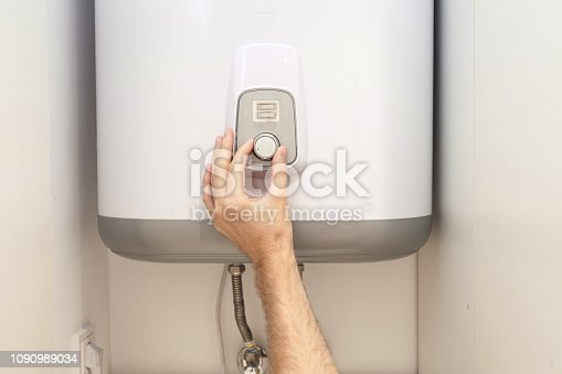 996279800istockphoto Close-up of man hands setting the temperature of water in Electric Boiler 1090989034