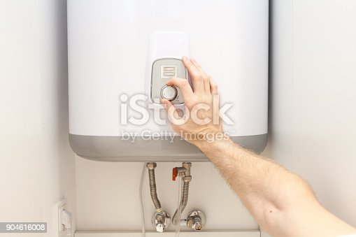 996279800istockphoto Close-up of man hands setting the temperature of water in Electric Boiler 904616008