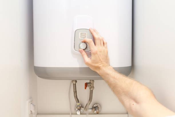 nahaufnahme der mannhände einstellung der temperatur des wassers in elektrischen boiler - heißes wasser stock-fotos und bilder