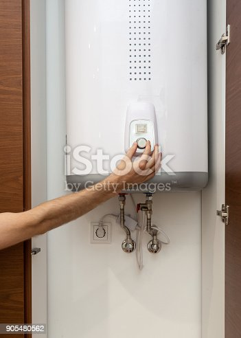 996279800istockphoto Close-up of man hands setting the temperature of water in Electric Boiler 905480562