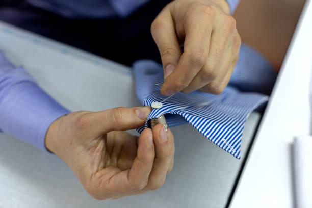Closeup de mãos de homem, um botão de costura - foto de acervo