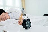 Closeup of man hitting alarm clock with hammer.