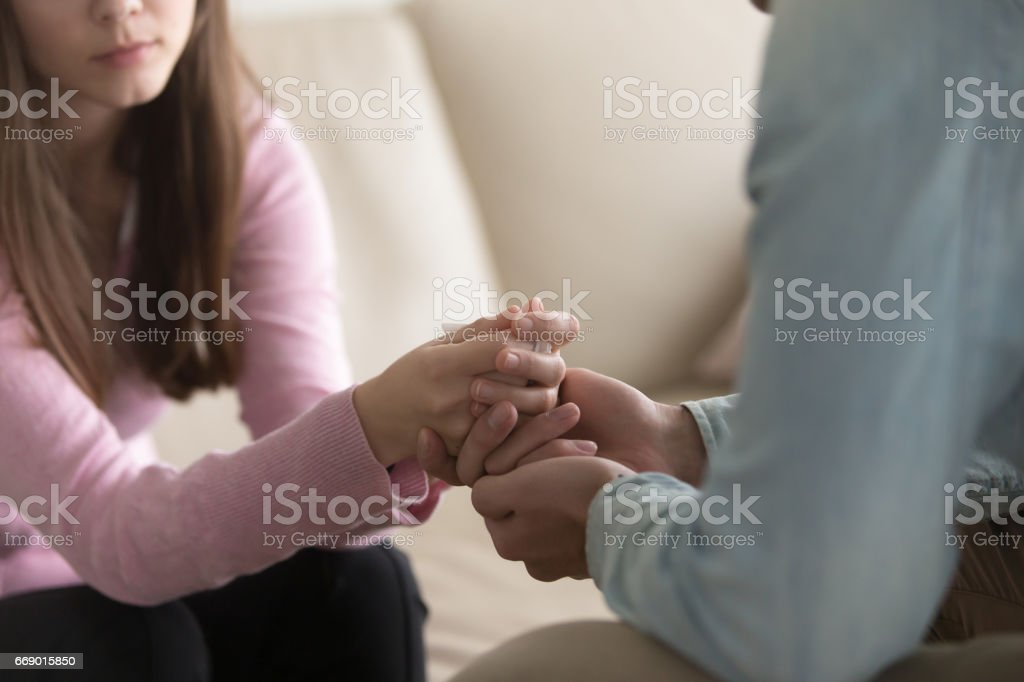 Closeup of man holding crying woman hands, compassion and comfort stock photo