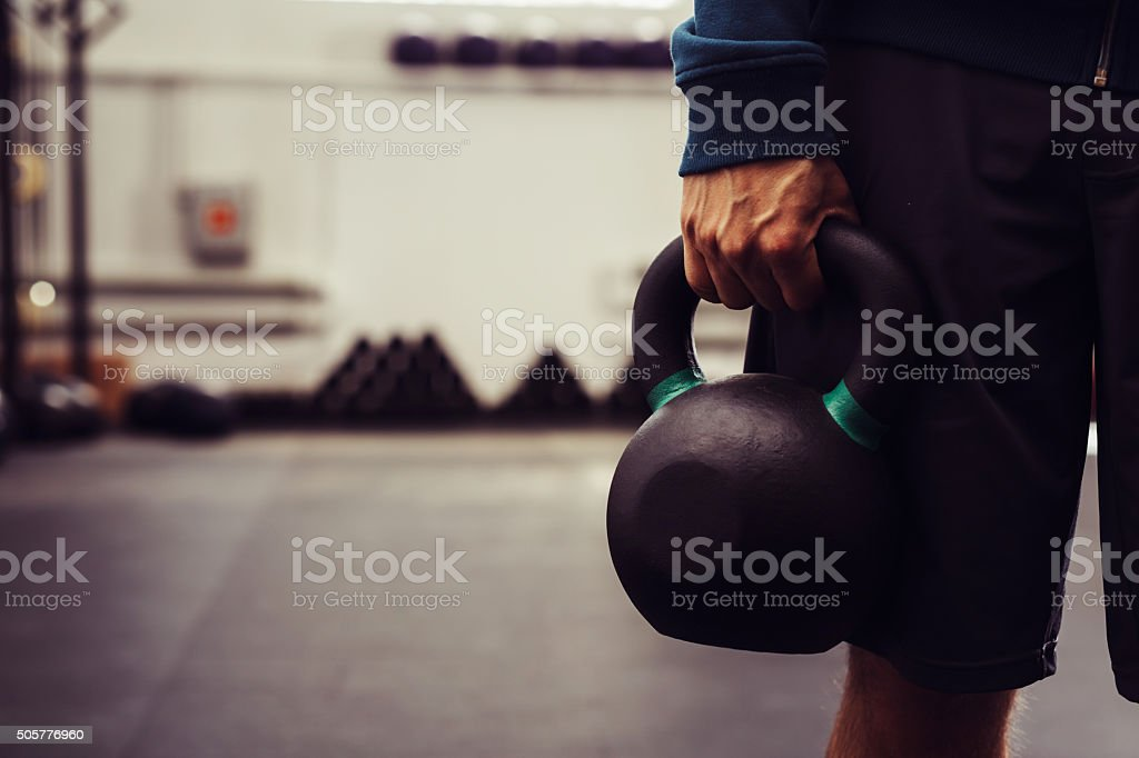 Close-up of man holding heavy kettlebell stock photo